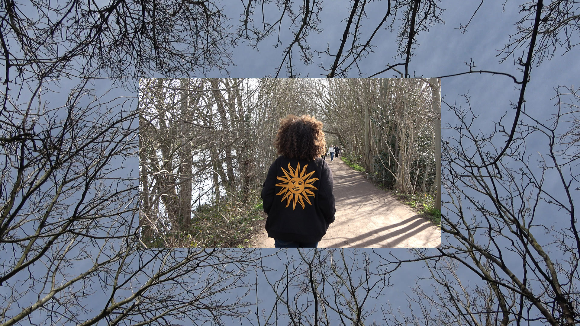 An image of Jamila from the back. She's walking down a pedestrian path lined by bare trees and a river on the left. Jamila is wearing a black jacket which has an image of a yellow sun with a face on the back. The image is overlaid on a larger image of blue sky with bare tree branches coming into the frame from all sides.
