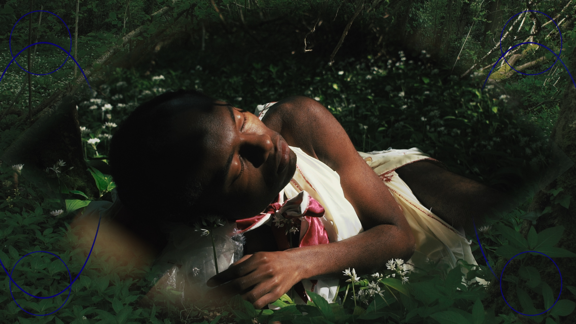 A close up of a person lying on the ground with their eyes closed. They're in a dark woodland under a small patch of sunlight. They're wearing white and surrounded by wild garlic flowers.